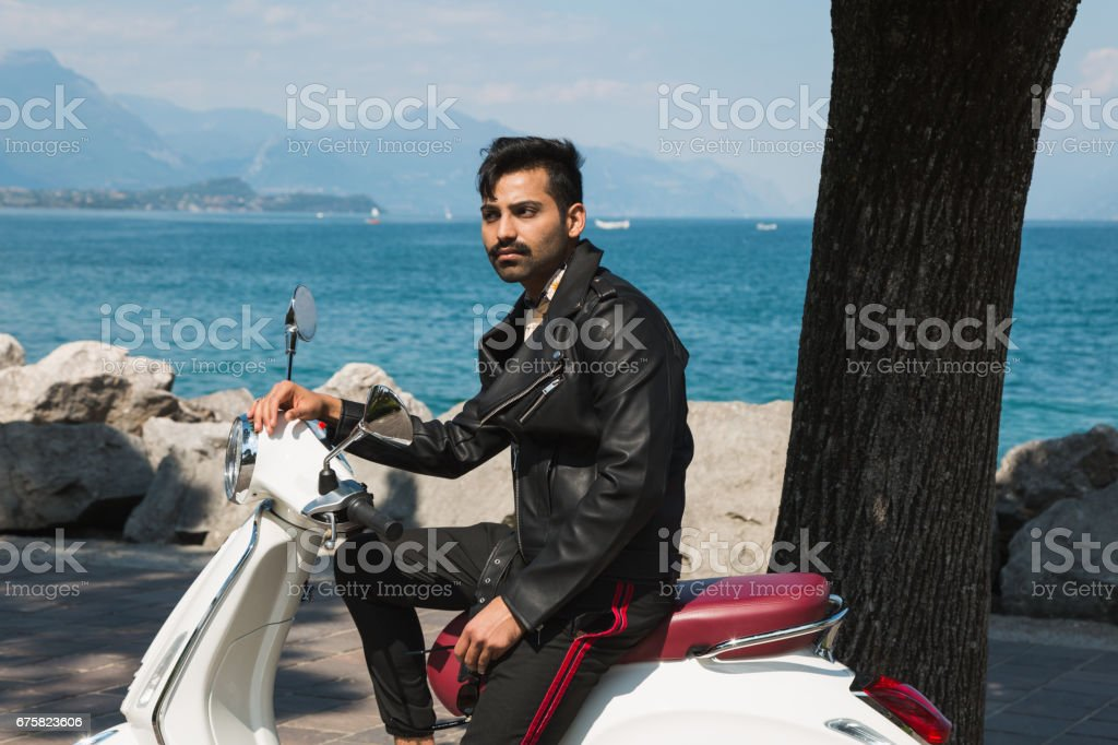Handsome Indian man posing on a scooter stock photo
