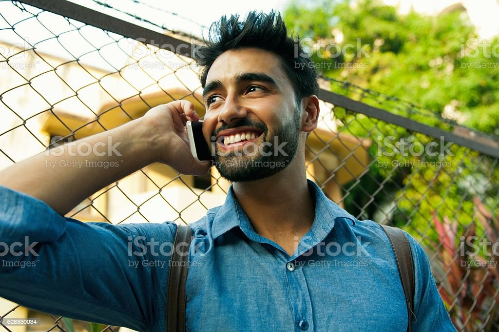 Handsome Indian man talking using mobile phone. stock photo