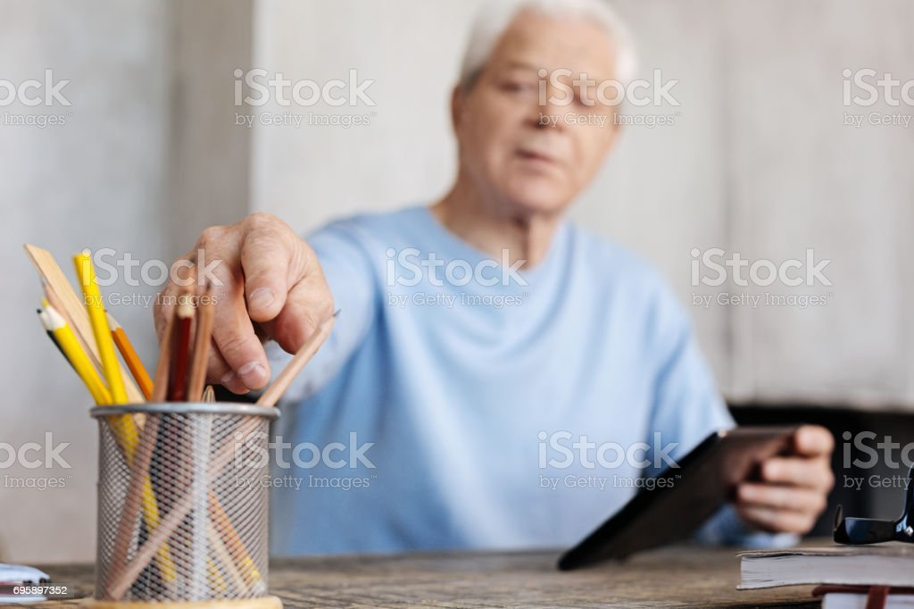 Handsome inspired gentleman reaching for a pencil stock photo