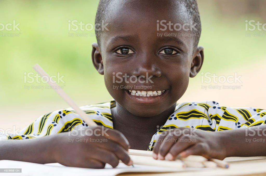 Handsome Little African Black Boy Toothy Smile in School Writing stock photo