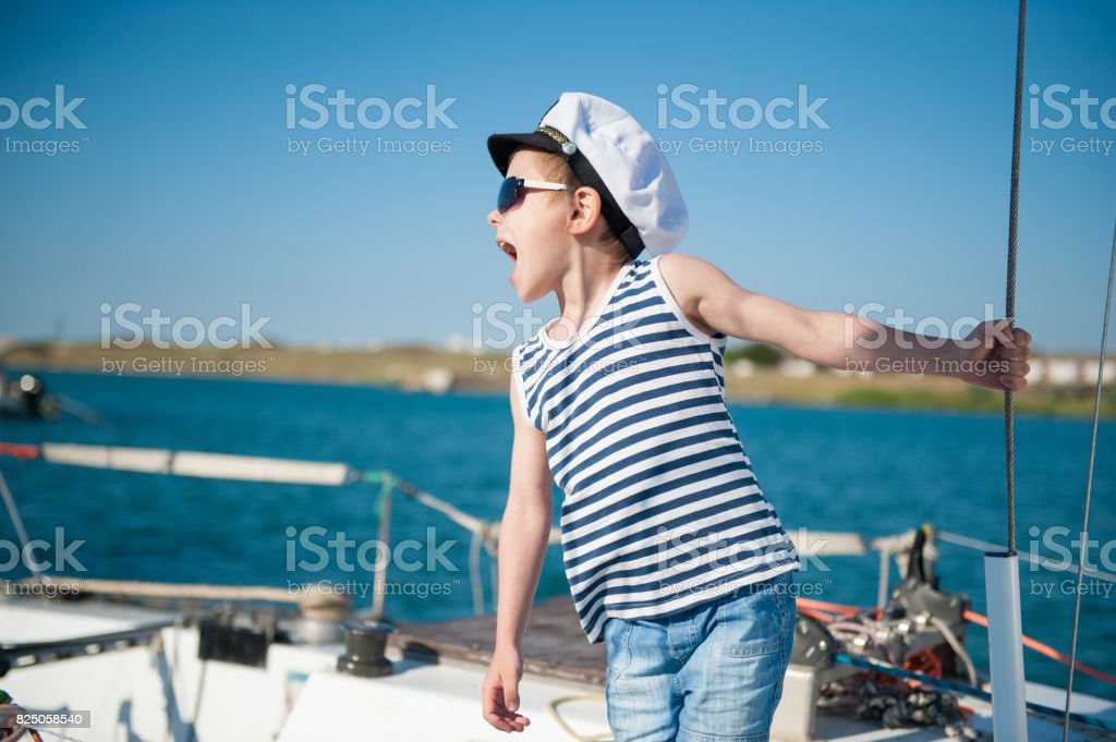 handsome little kid wearing sailor shirt and captain hat and sunglasses giving orders stock photo