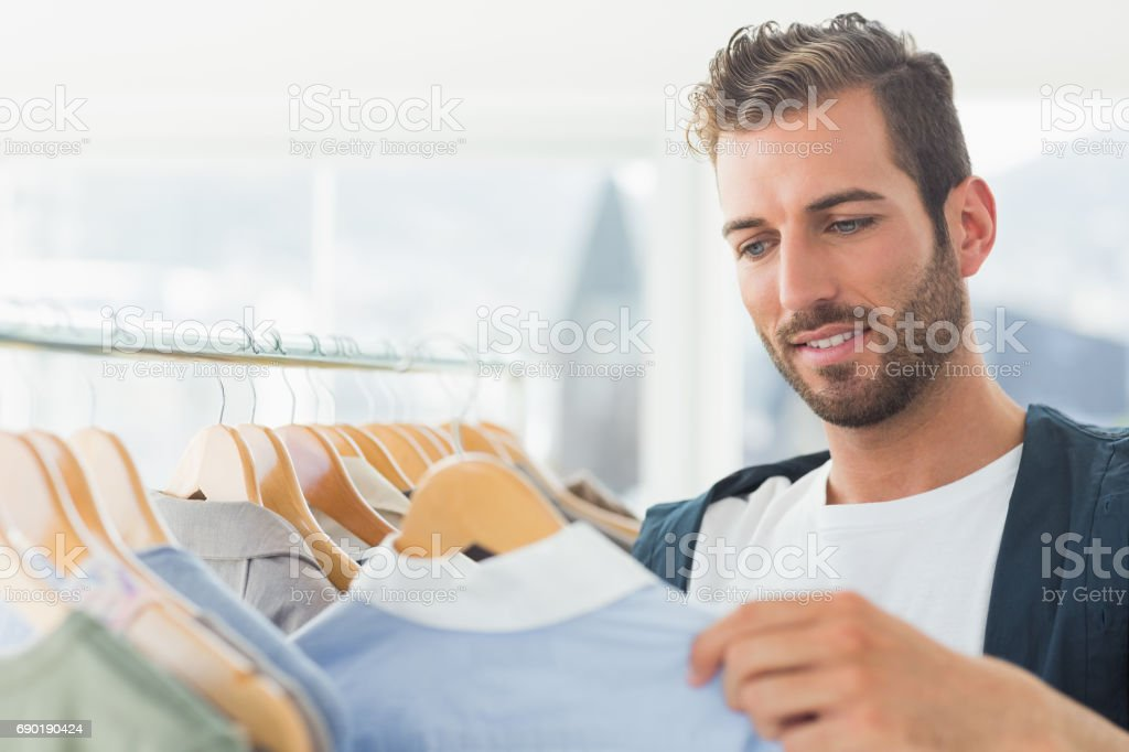 handsome male customer by clothes rack stock photo