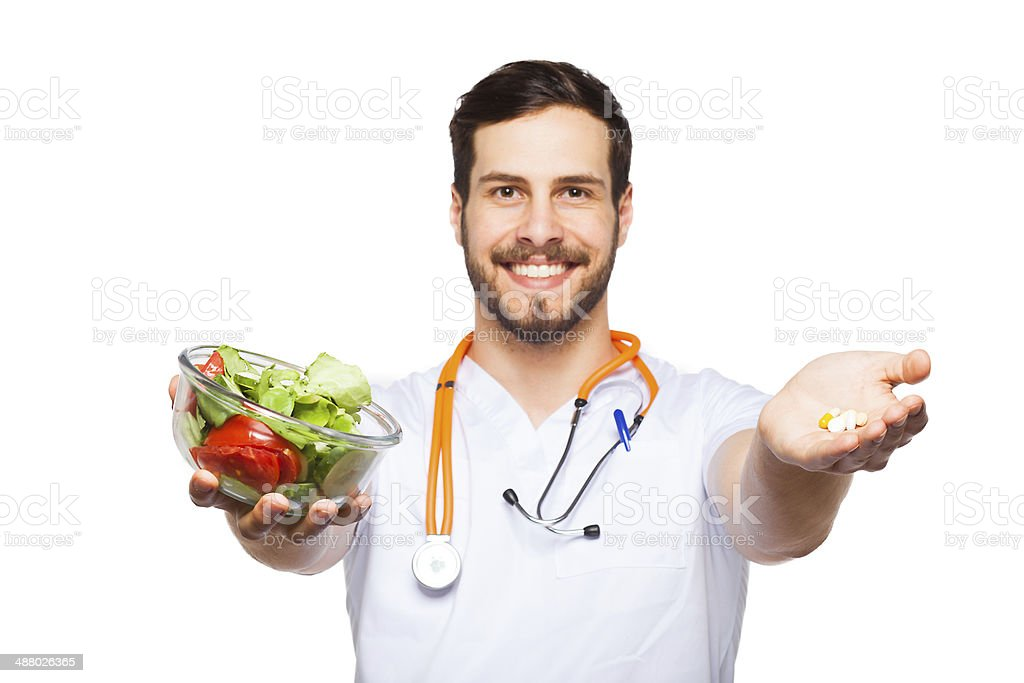 Handsome male doctor showing salad and pills stock photo