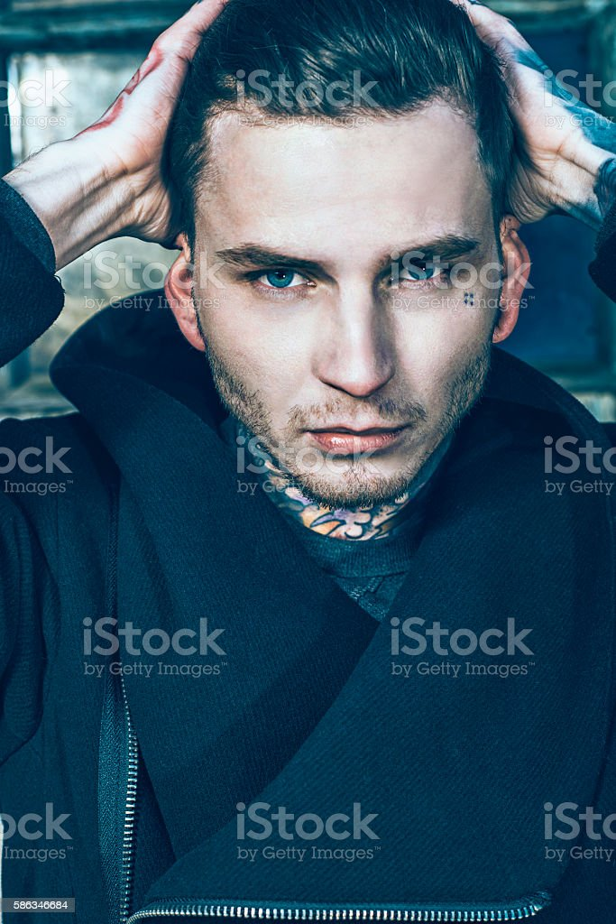 Handsome male fashion model with tattoos on his face stock photo