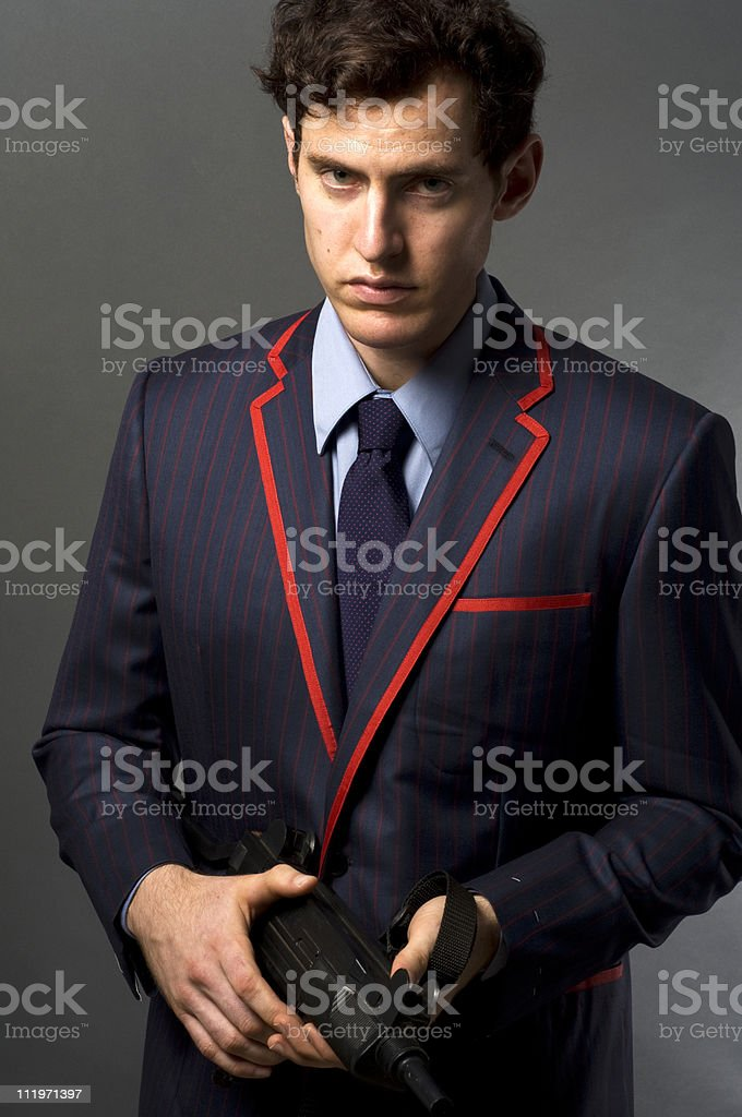 Handsome Male In A Designer Suit Sporting An Uzi stock photo