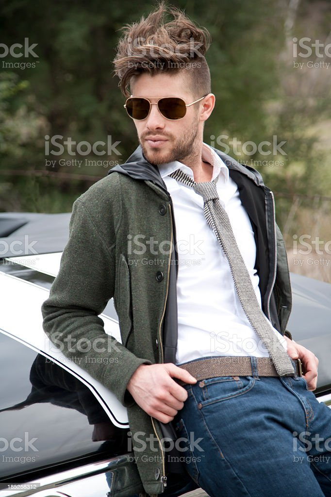 Handsome male model sitting on the back of a black car royalty-free stock photo