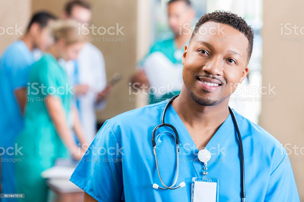 Handsome male nurse attends staff meeting stock photo