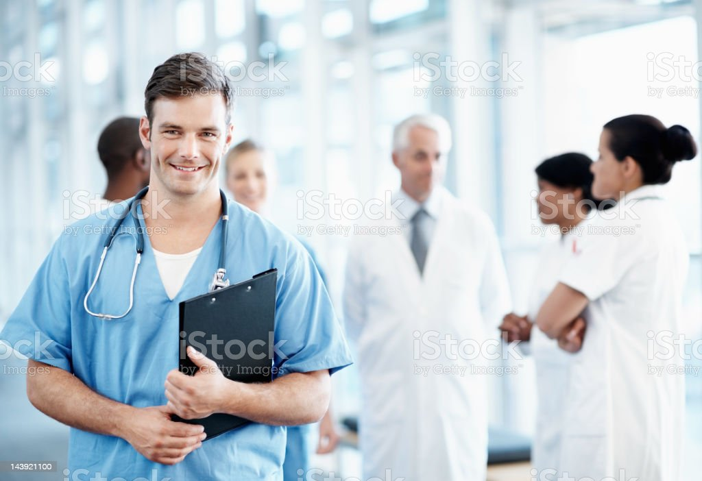 Handsome male nurse with medical team in background stock photo