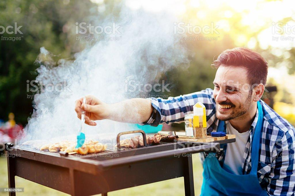 HAndsome male preparing barbecue stock photo
