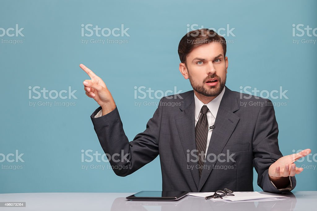 Handsome male reporter is working at studio stock photo