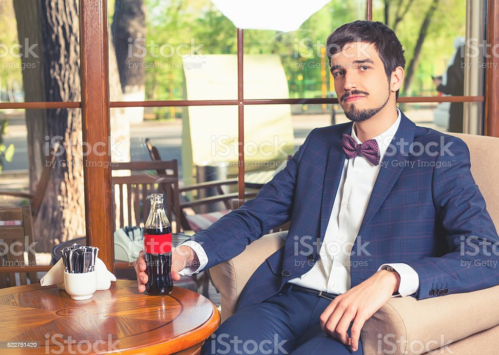 Handsome male sitting at cafe and holding fresh drink cola stock photo