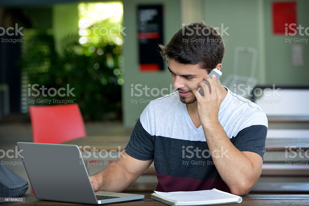 Handsome male student sitting and working on a laptop computer stock photo