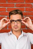 handsome man adjusts his glasses