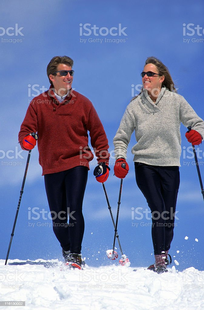 Handsome Man and Beautiful Woman Snowshoeing stock photo