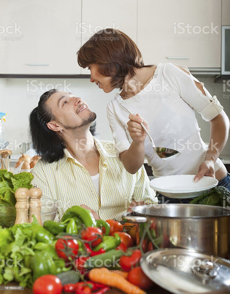 Handsome man and beautiful woman with vegetables in the kitchen royalty-free stock photo