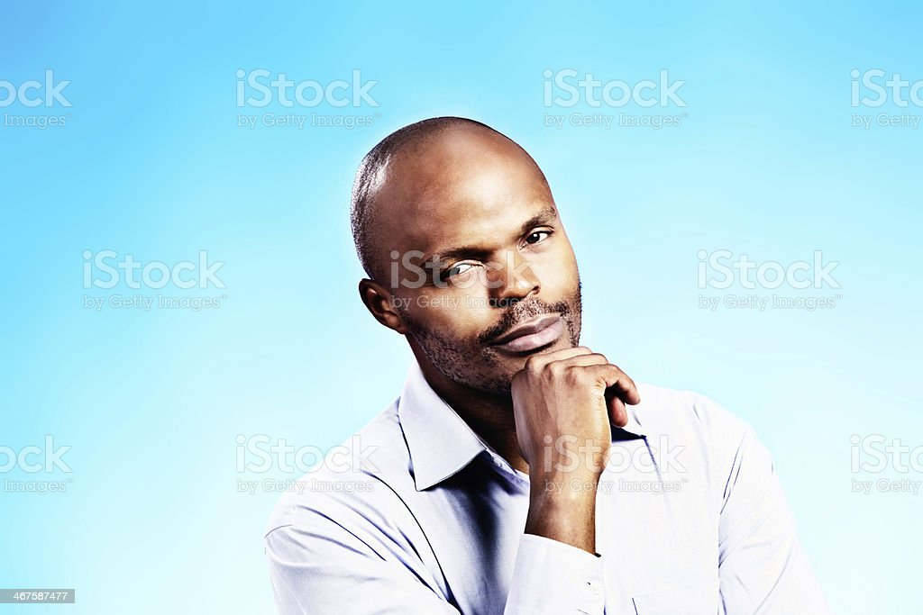 Handsome man, chin on hand, smiles gently at camera royalty-free stock photo