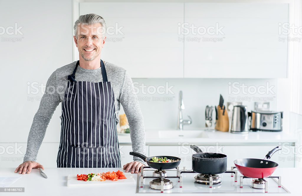 Handsome man cooking at home stock photo