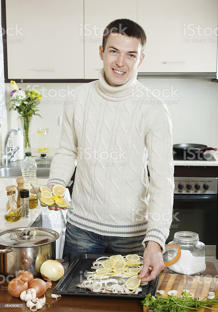 Handsome man cooking raw fish with lemon royalty-free stock photo