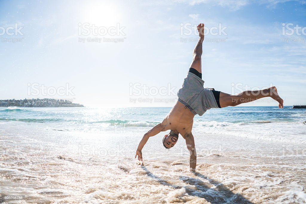 Handsome man doing a cartwheel at the beach stock photo