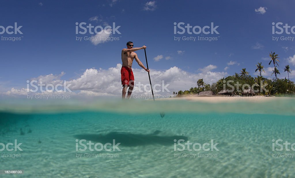 A handsome man doing a stand-up paddle boarding royalty-free stock photo