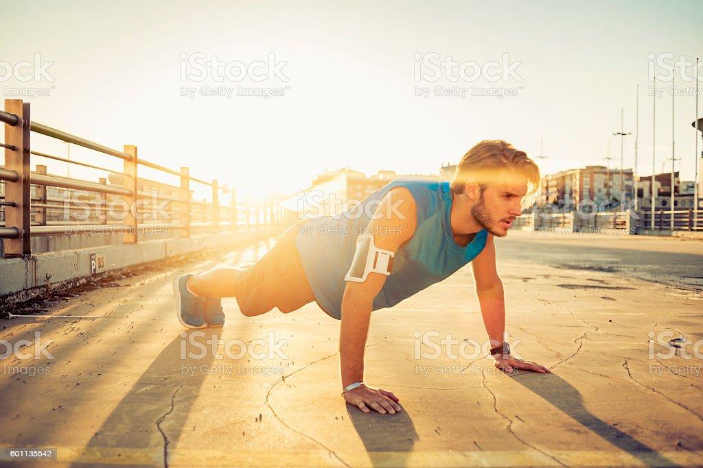 handsome man doing push ups stock photo