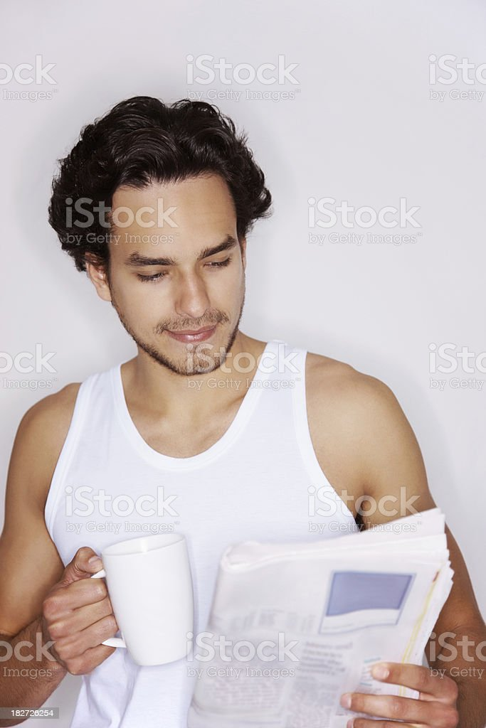 Handsome man drinking coffee and reading a newspaper royalty-free stock photo