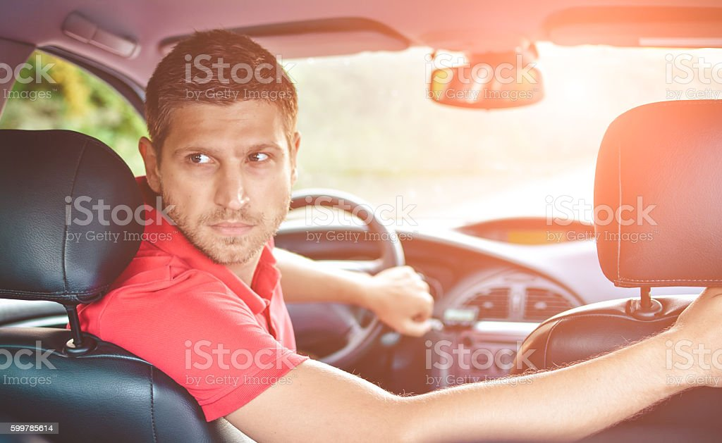 Handsome man driver looking back and parking car stock photo