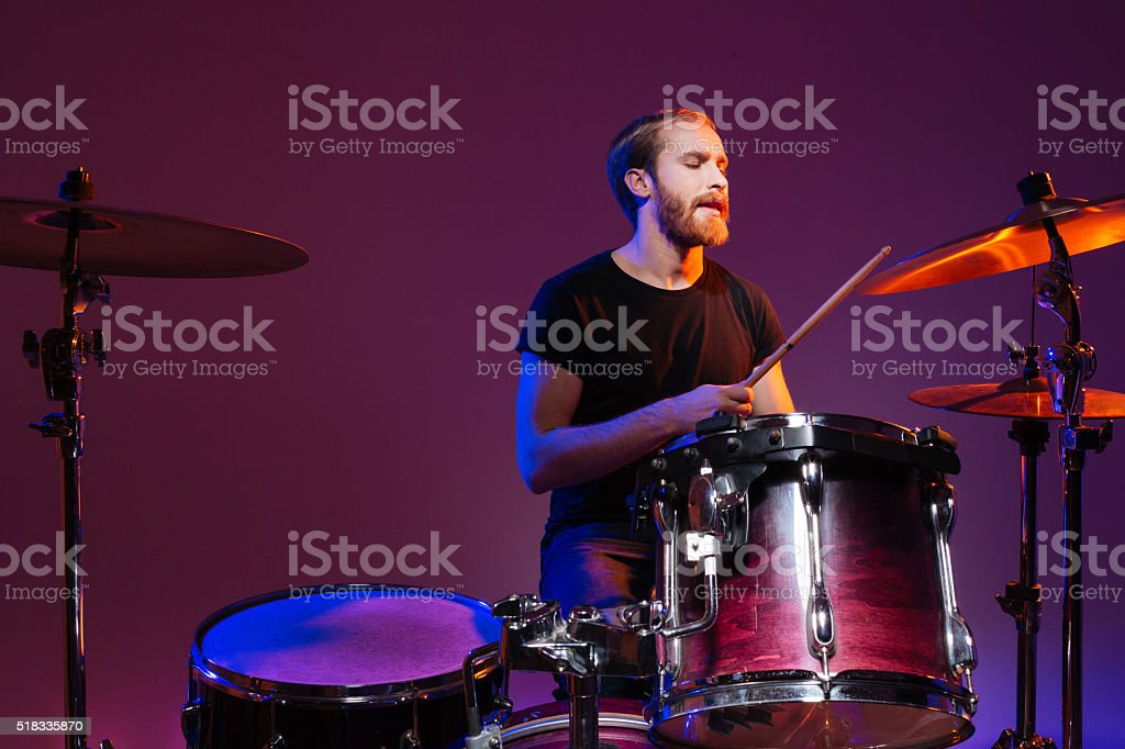 Handsome man drummer sitting and playing on his kit stock photo