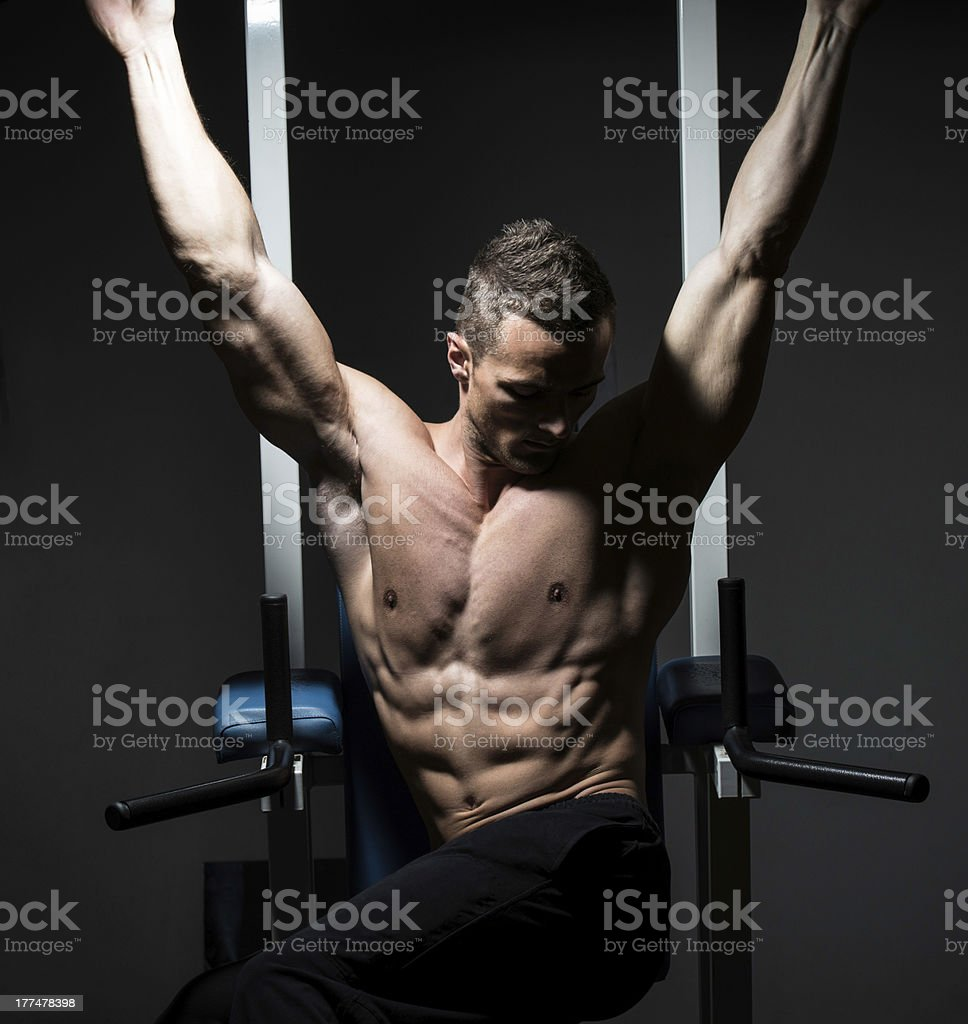 handsome man exercising his abs at the gym royalty-free stock photo