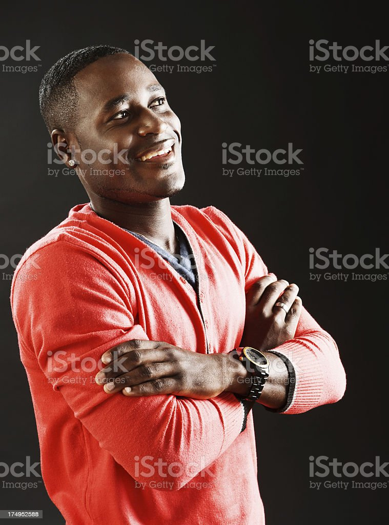 Handsome man folds arms, looks to side smiling stock photo