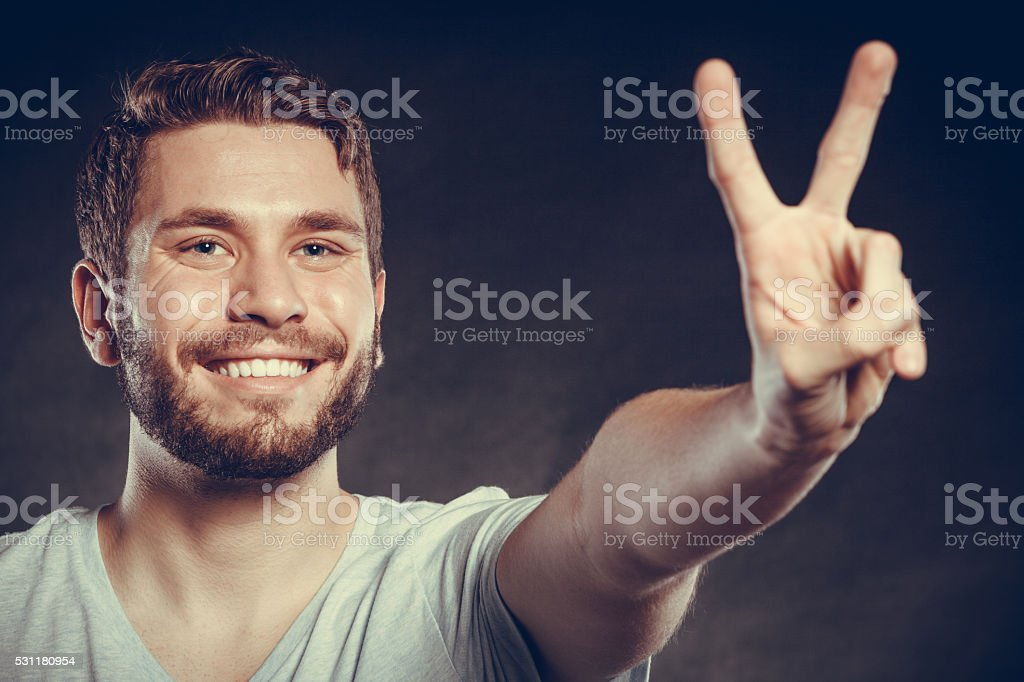 Handsome man guy giving peace v sign gesture. stock photo
