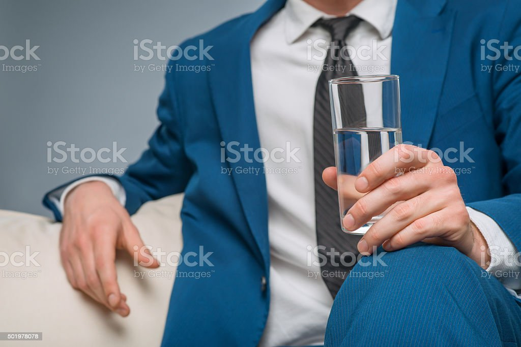 Handsome man holding a glass of water stock photo