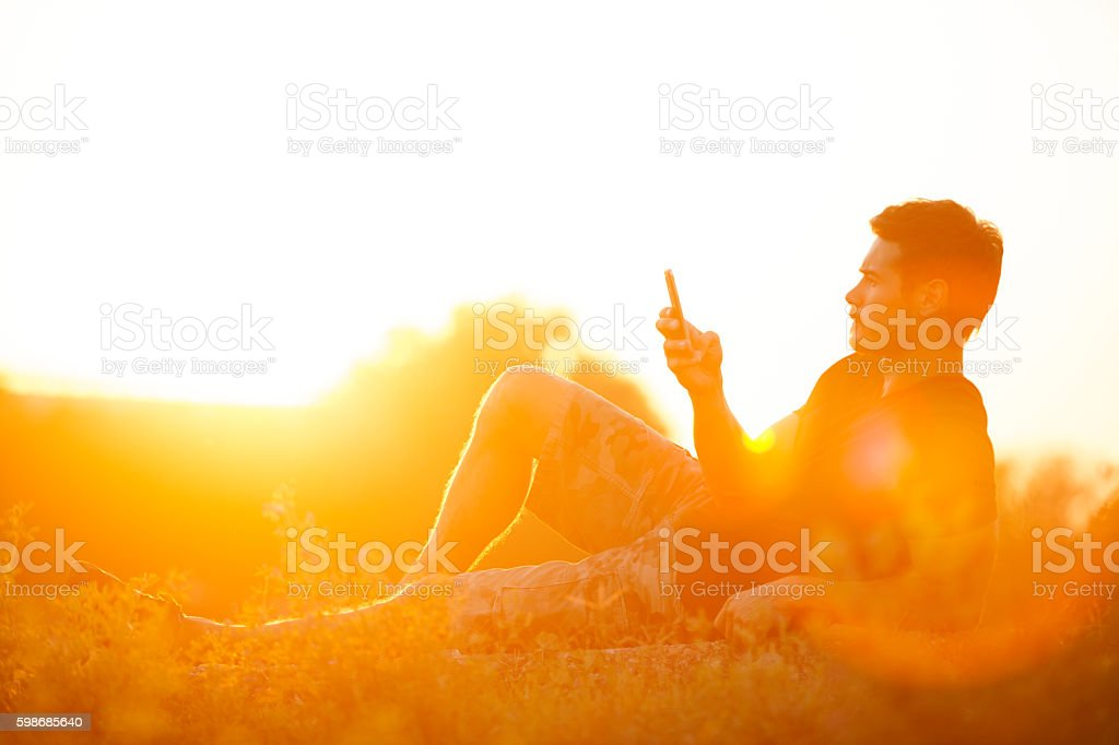 Handsome Man Holding and Looking At Mobile Smart Phone Outdoors stock photo