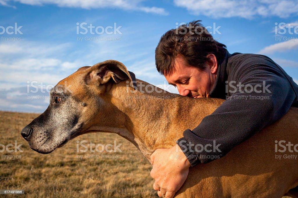 Handsome man hugging his dog stock photo