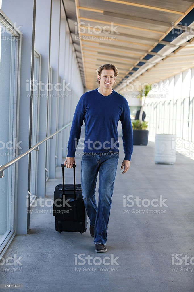 Handsome man in an airport with a suitcase. royalty-free stock photo