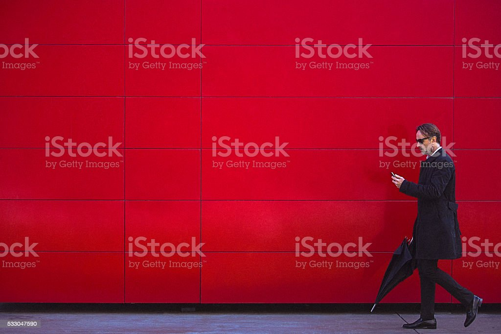 Handsome man in black walking beside the red wall stock photo