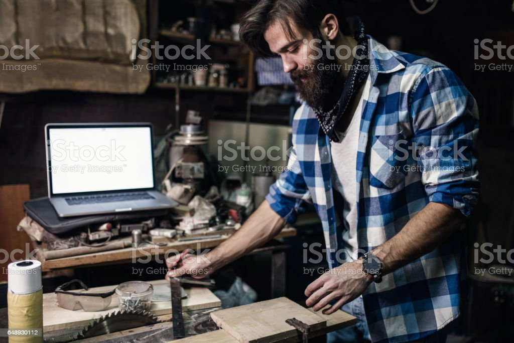 Handsome man in casual clothes taking measures with a ruler stock photo