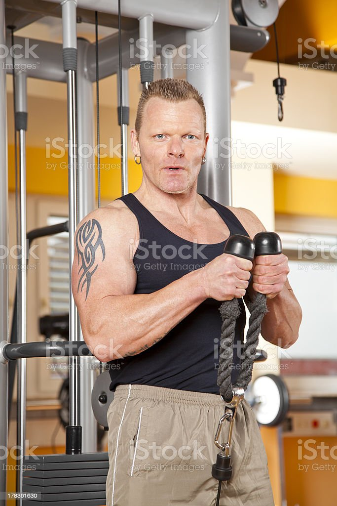 handsome man in forties exercising at gym training biceps stock photo