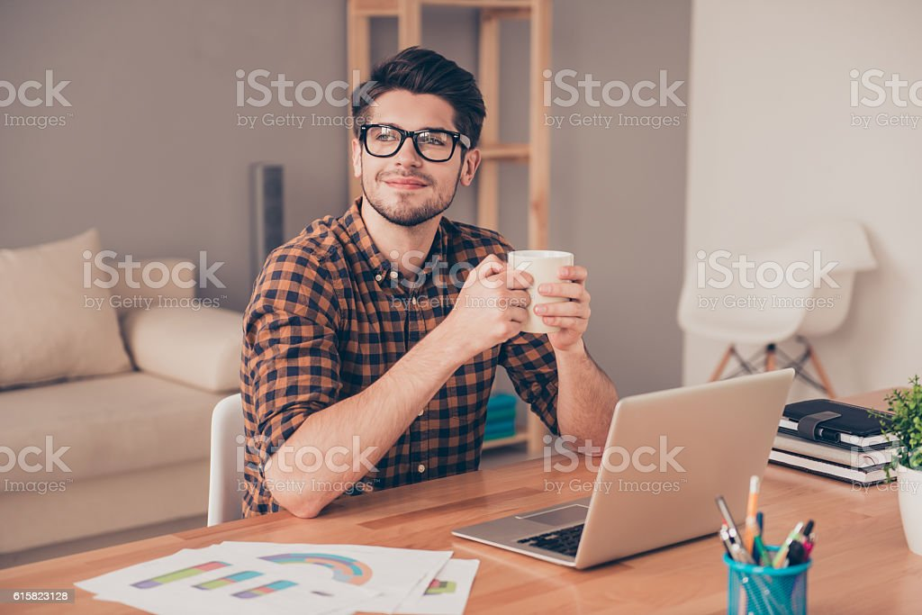handsome man in glasses drinking coffee in office and dreaming stock photo