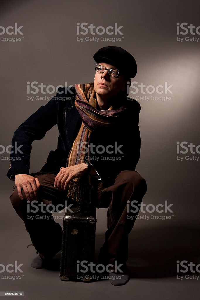 handsome man in glasses sitting on suitcase royalty-free stock photo
