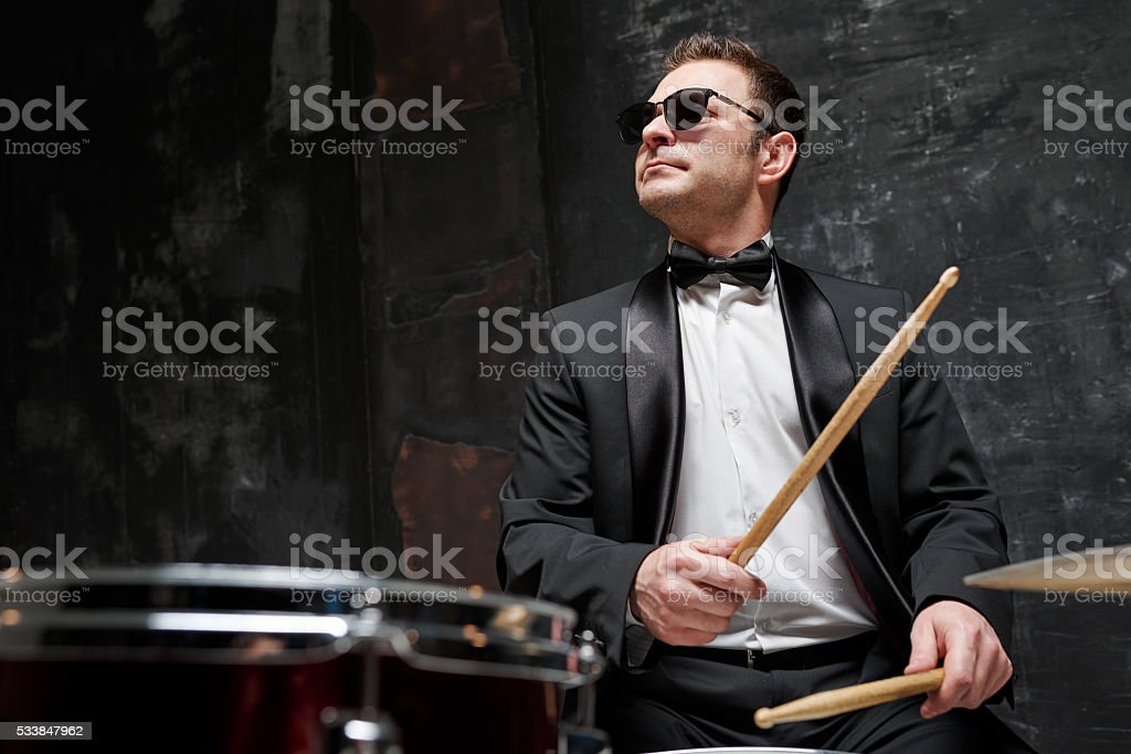 Handsome man in sunglasses and suit playing a drum stock photo