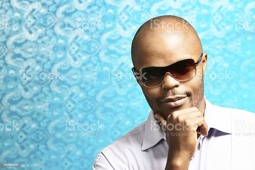 Handsome man in sunglasses smiles flirtatiously against shimmering blue background royalty-free stock photo