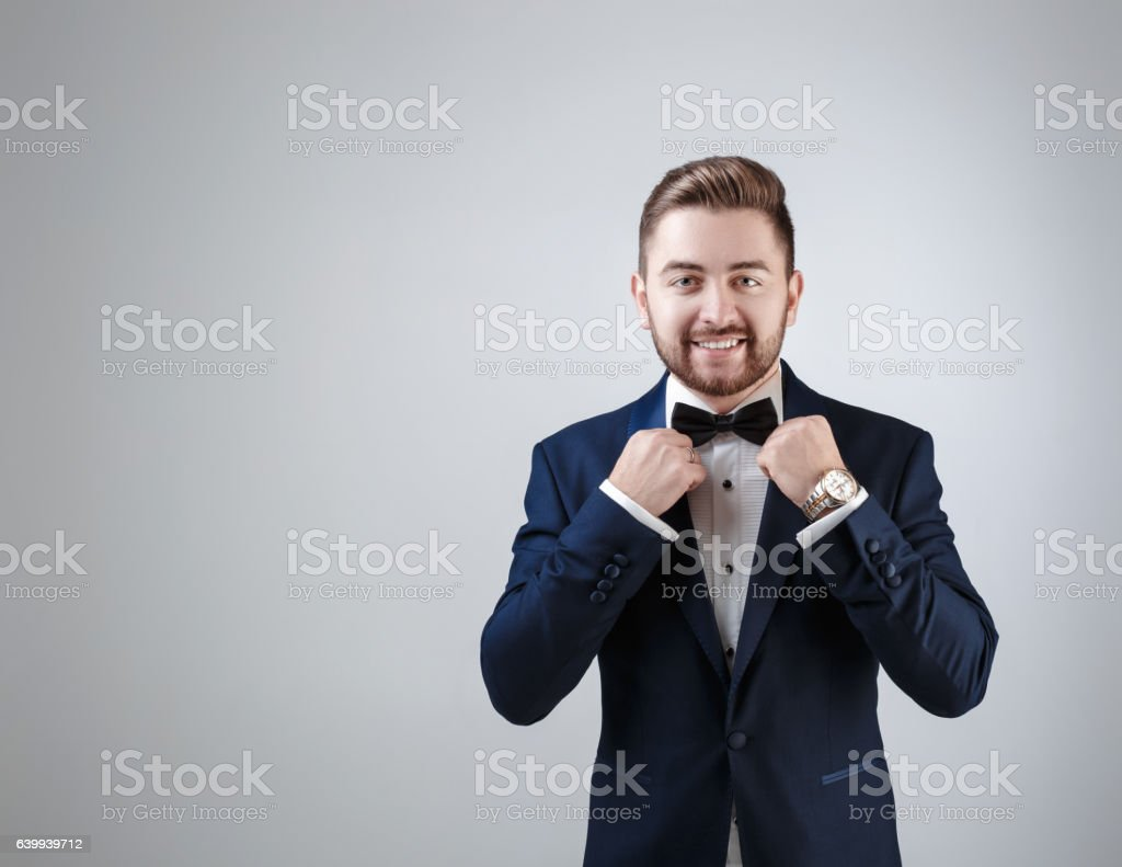 Handsome man in tuxedo and bow tie looking at camera stock photo