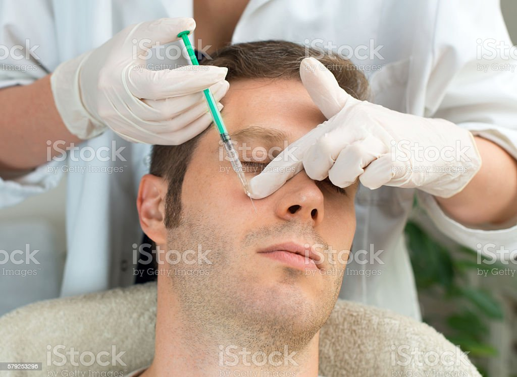 Handsome man is getting injection. Concept of aesthetic beauty. stock photo