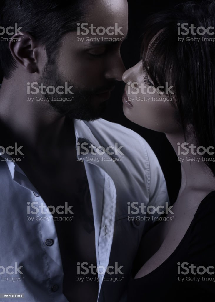 Handsome man kissing a beautiful woman stock photo