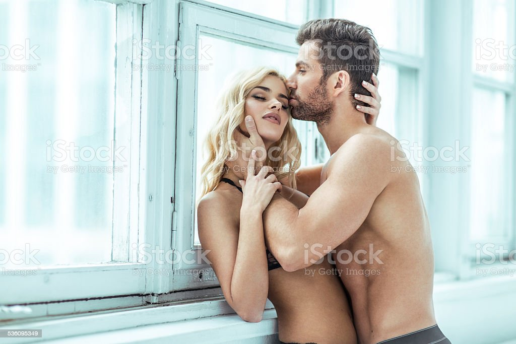 Handsome man kissing blond beauty stock photo