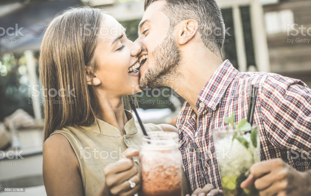 Handsome man kissing young woman at fashion cocktail bar - Happy couple of lovers at beginning of love story - Drunk feelings concept with boyfriend and girlfriend on retro filter - Focus on faces stock photo