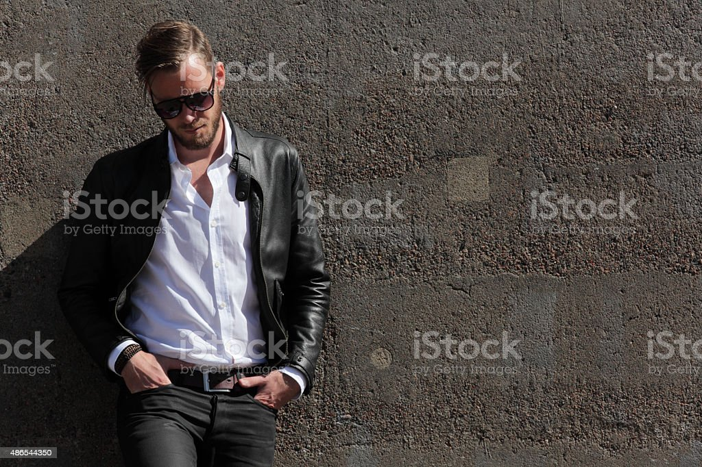 Handsome man leaning against a wall stock photo
