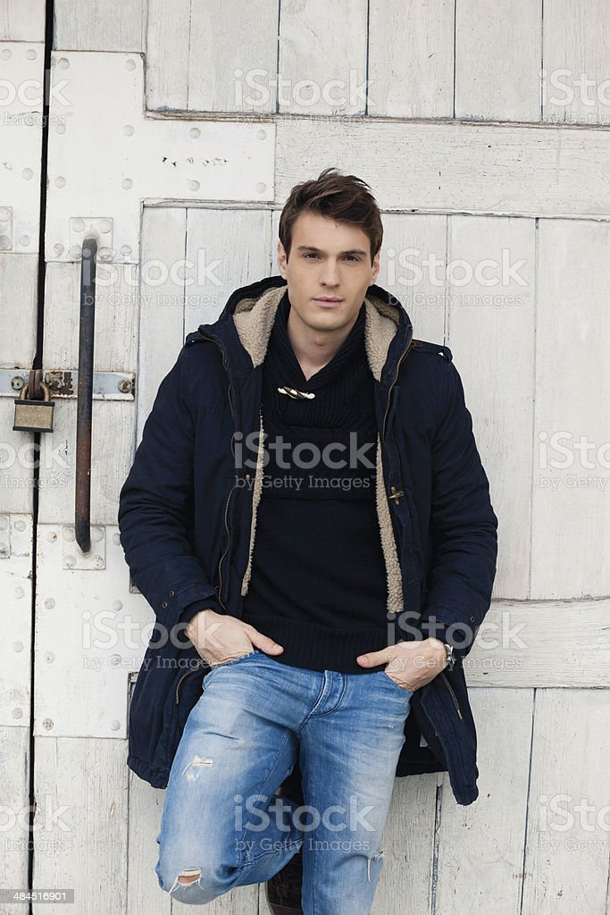 Handsome man leaning against big white wooden door stock photo