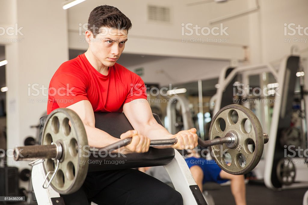 Handsome man lifting weights at the gym stock photo
